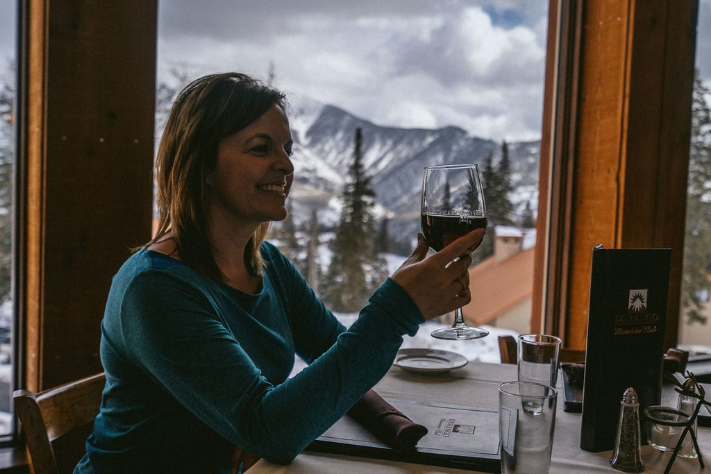 woman drinking wine with mountains in background