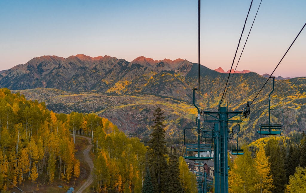 looking down a chairlift line with mountains and aspens at twilight